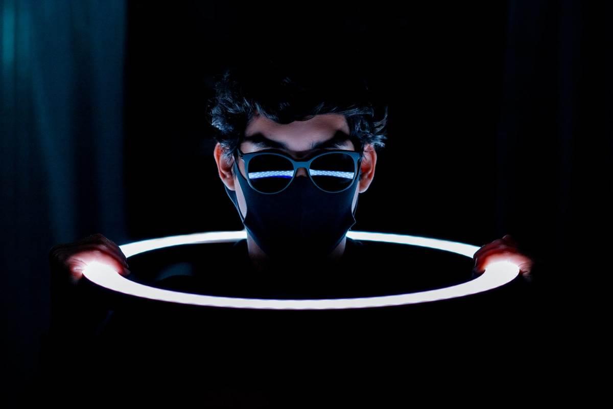 Haker sa maskom i naočarima izvviruje iz svetlog prstena