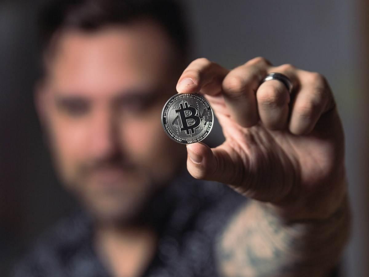 Čovek drži Bitcoin novčić u ruci