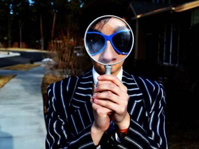 Devojka sa naočarima gleda kroz lupu